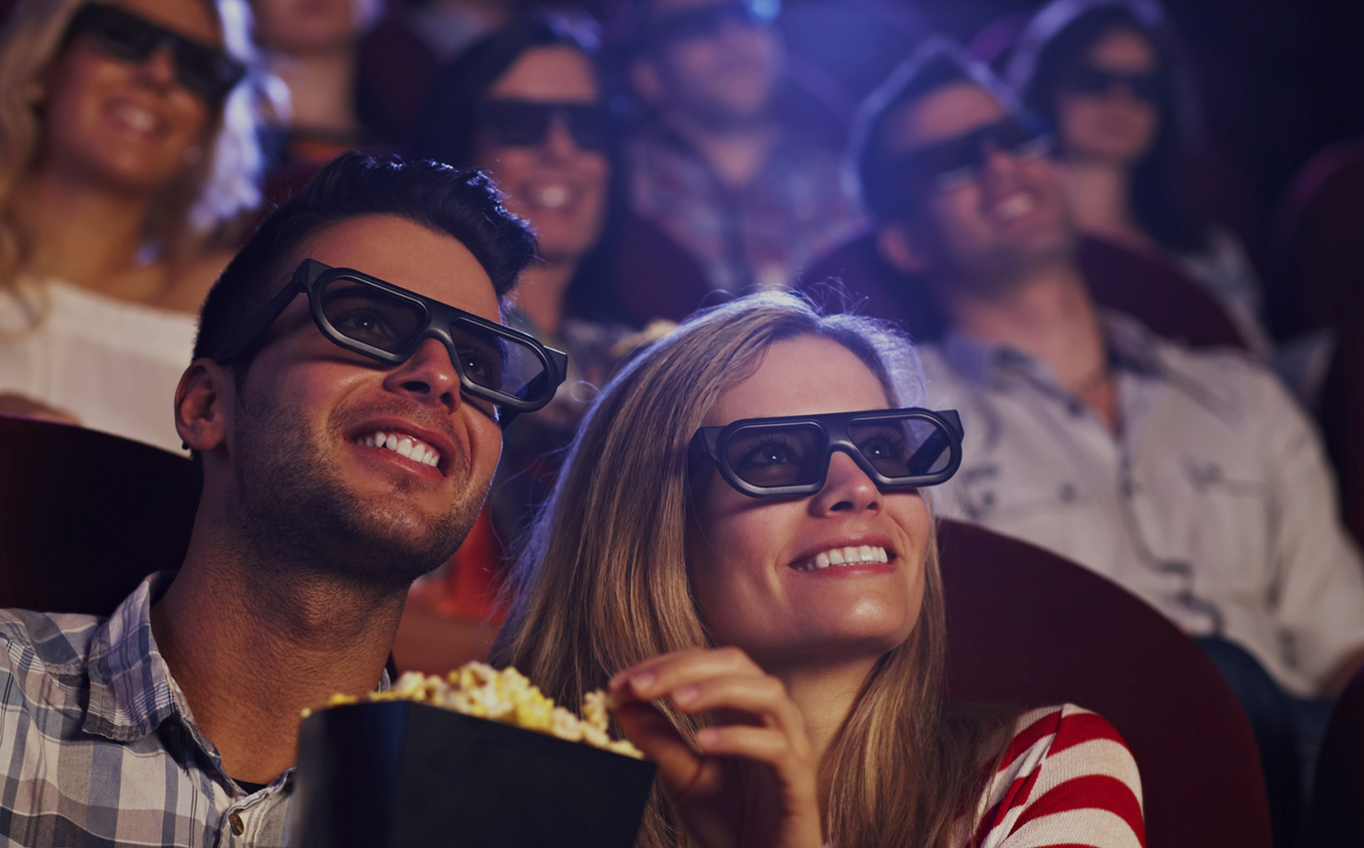 A man and woman at the cinema with 3D glasses enjoying popcorn.