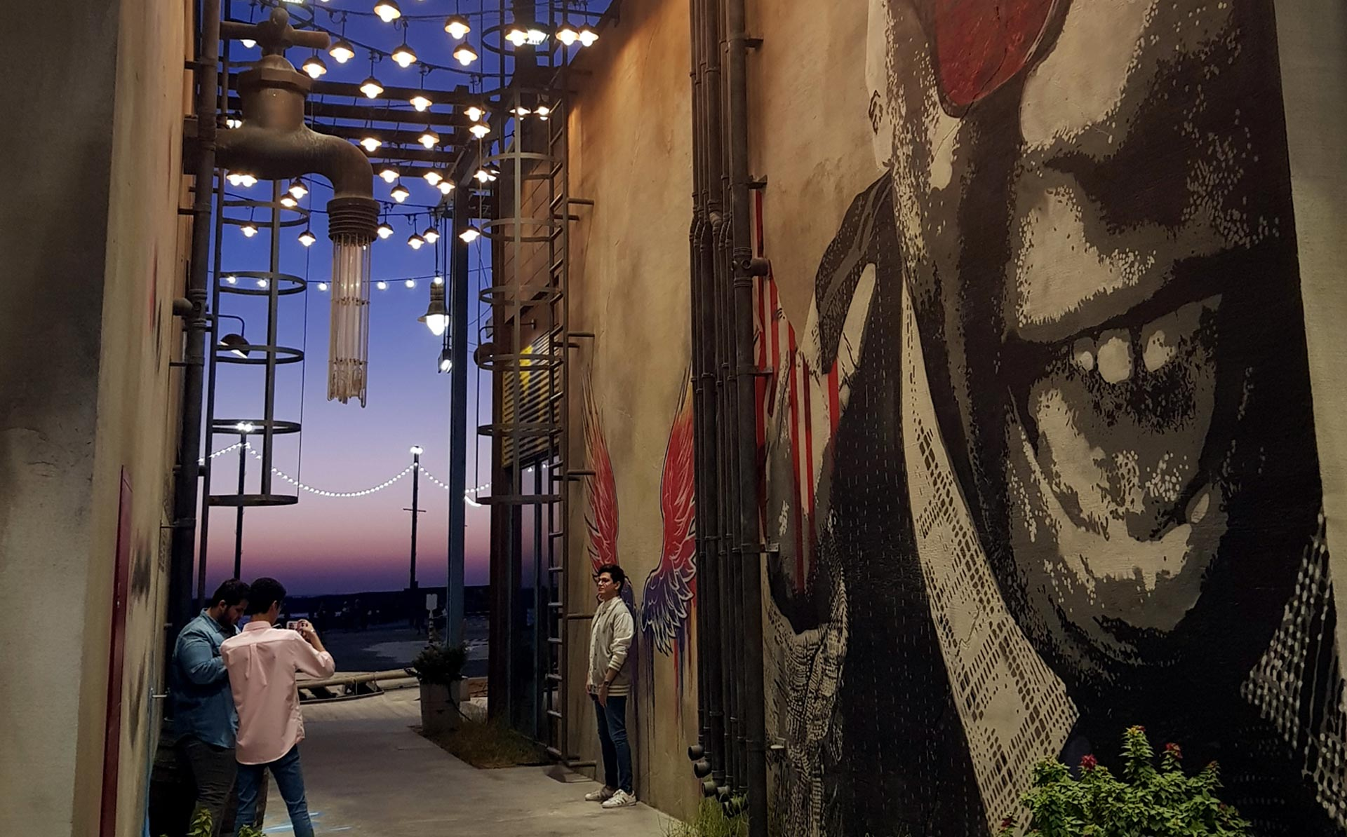 People taking photos at La Mer, Dubai at sunset with graffiti art on the wall.